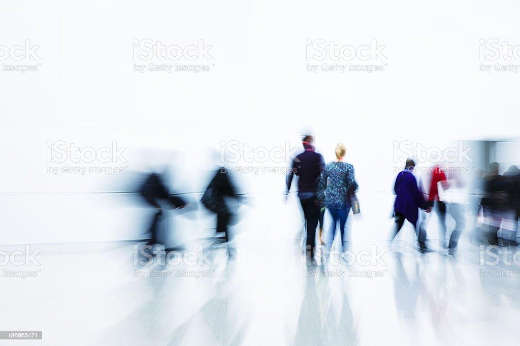 Blurred people walking toward a door in a hallway royalty-free stock photo
