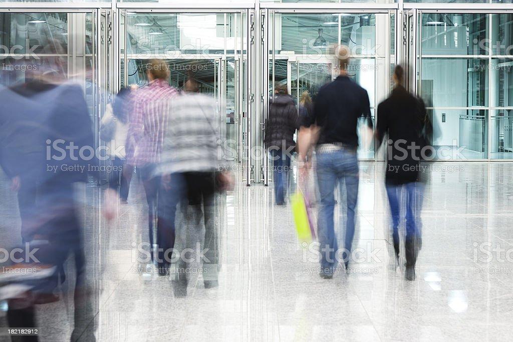 Blurred People Walking Toward Glass Doorway royalty-free stock photo