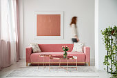 Blurred person against the wall with painting in white flat interior with plant and millenial pink couch. Real photo