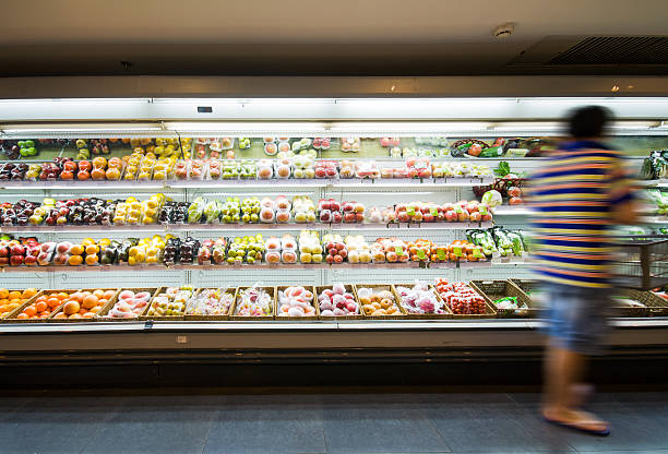 Blurred person stands by shelf with fruits in supermarket stock photo