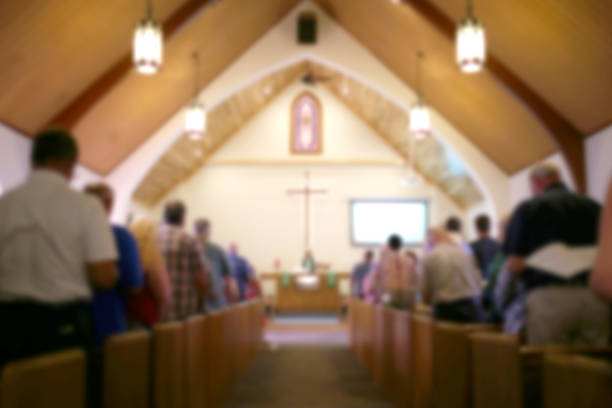 Blurred Photo of the Iterior of a Church Sanctuary with Congregation, Pastor, and a Large Cross Visible A blurred photo of the inside of a church sanctuary that is filled with people in the pews, and the pastor stands under a large cross at the altar. clergy stock pictures, royalty-free photos & images