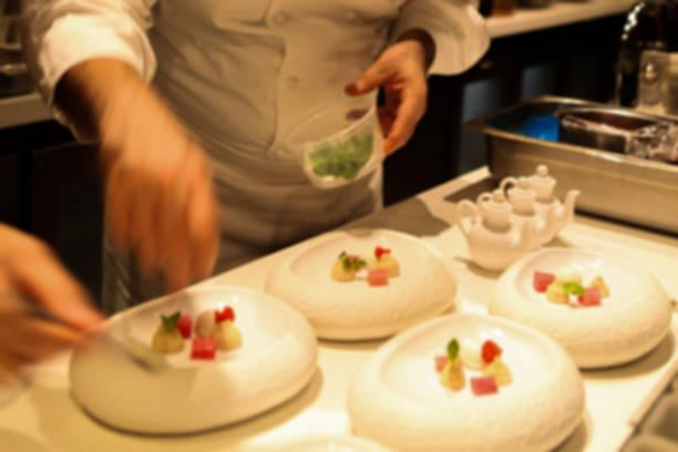 verschwommen. professional-sternekoch in aktion: beschichtung eine exquisite dessert in einem stilvollen schüssel weiß. unschärfe. - kochkunst stock-fotos und bilder