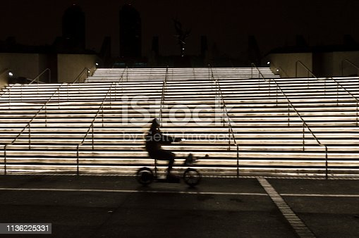 812812808istockphoto Blurred Profile of Electric Bike Rider at Night in Front of a Lit Staircase 1136225331