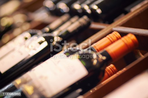 Blurred racks with bottles of red wine. Shelves with bottles of wine in a large grocery supermarket. Basic background for design