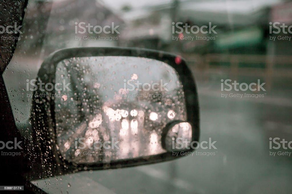 blurred rain drop on car window in rainy day in dark tone