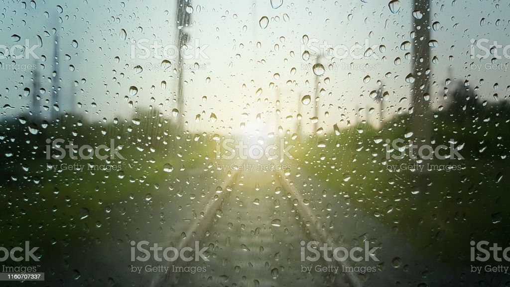 Raindrops on a window with a blurred railway road background.