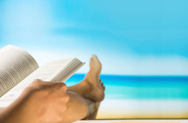 Blurred reading book and relax on beach table with sea view stock photo