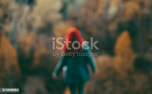 istock Blurred redhead girl standing over green and yellow trees 910698884