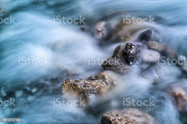 Photo of blurred river motion water and stones