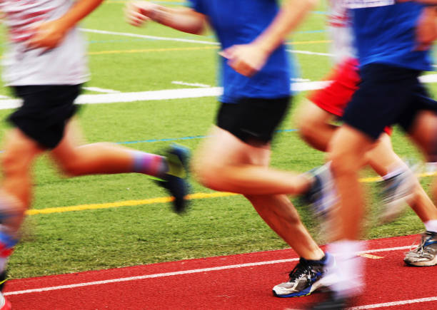 blurred runners on a track - high school sports stock pictures, royalty-free photos & images