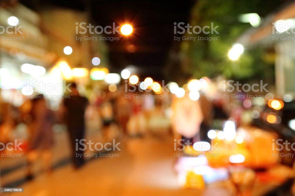Blurred scene of tourists walk in night market. stock photo