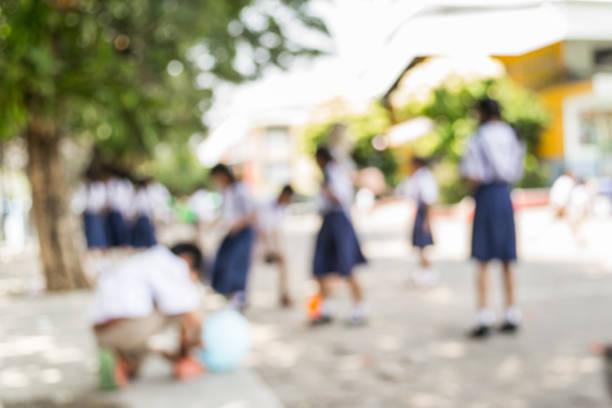 verschwommene schoolchild spielen unter baum - vorschuldekorationen stock-fotos und bilder