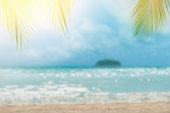 Blurred seascape island,water bokeh and sand beach against sunlight background with palm leaf on foreground