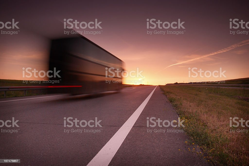 Blurred semi-truck on highway in the sunset stock photo