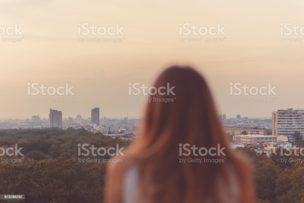 Blurred silhouette of a girl looking at the Belgrade, Serbia landscape. stock photo