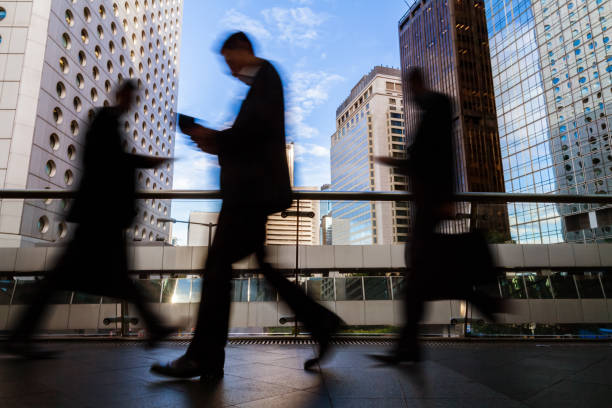 Blurred silhouettes of businesspeople walking at footbridge in Central District Hong Kong stock photo