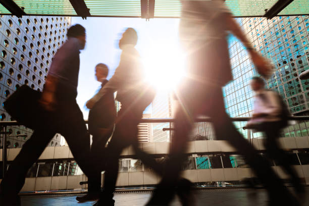 Blurred silhouettes of businesspeople walking in Hong Kong's Central District elevated walkway stock photo