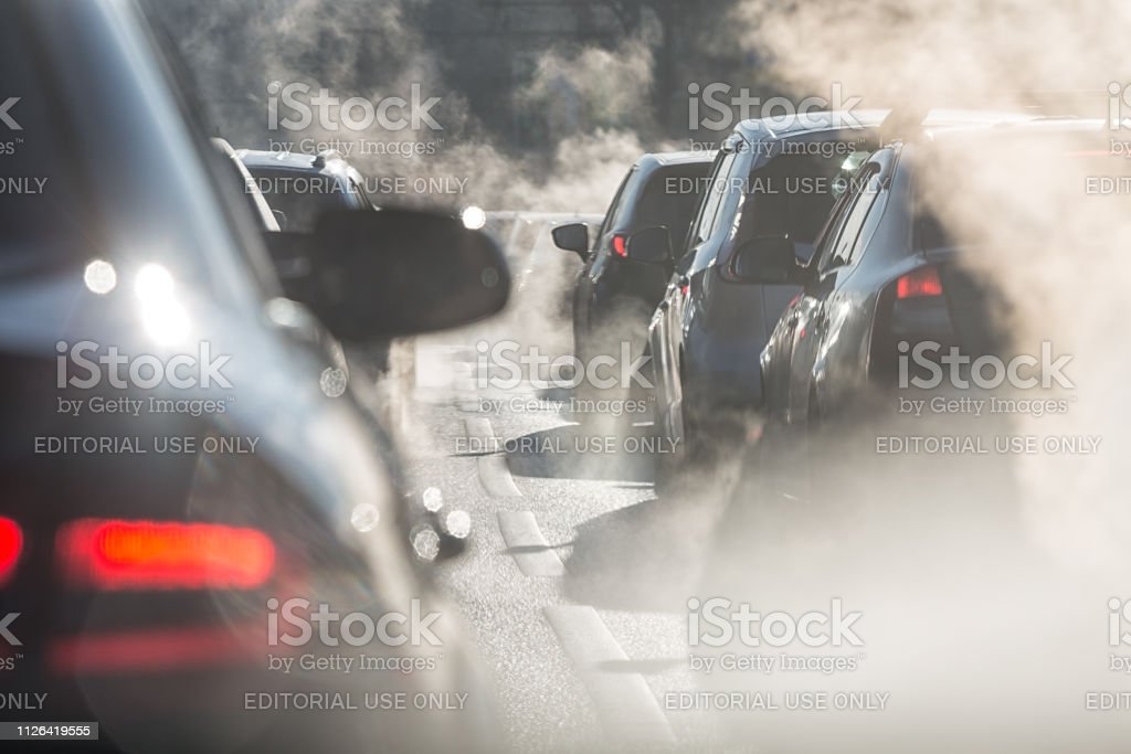 Blurred silhouettes of cars surrounded by steam from the exhaust pipes Moscow, Russia - August 08, 2017: Traffic jam. Blurred silhouettes of cars surrounded by steam from the exhaust pipes. Environmental pollution Asphalt Stock Photo
