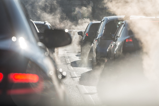 Blurred Silhouettes Of Cars Surrounded By Steam From The Exhaust Pipes Stock Photo - Download Image Now