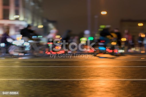 929609038istockphoto Blurred style background of riding cyclists. Parade of bicyclists in city, night, abstract. Modern active lifestyle, healthy lifestyle concept 948188864