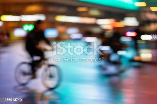 929609038istockphoto Blurred style background of silhouette of abstract unrecognizable man, riding bike, night city, illumination bokeh, motion blur. Healthy lifestyle, leisure activity concept. 1186913740