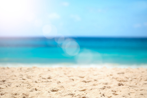 Blurred summer background, nature of tropical golden beach with rays of sun light. Golden sand beach, sea water against blue sky with white clouds. Copy space, summer vacation concept.