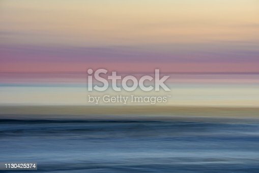 A long exposure of a beach sunset taken while moving the camera to create a blurring effect