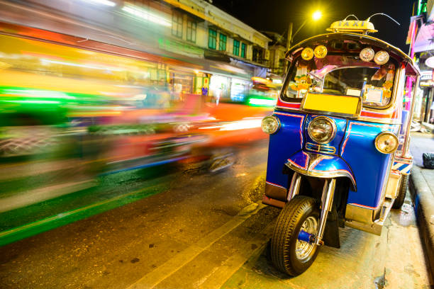 Blurred Traffic Passing a Parked Tuk Tuk Taxi, Bangkok, Thailand stock photo