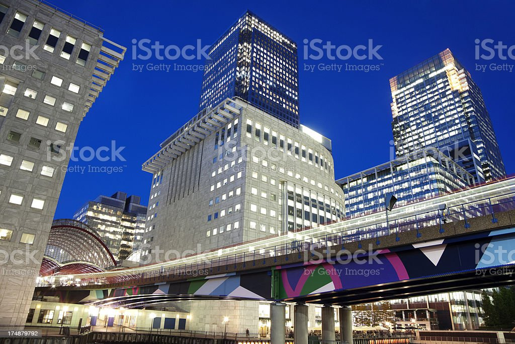 Blurred Train Between Office Buildings in Canary Wharf, London, England stock photo