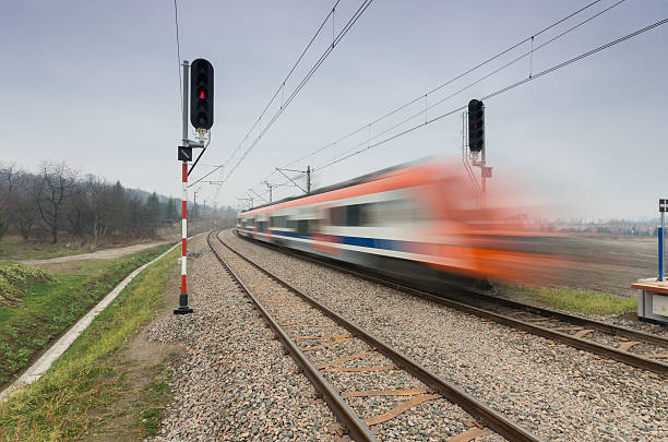 blurred train of koleje malopolskie on double railway track - railway signal stock photos and pictures