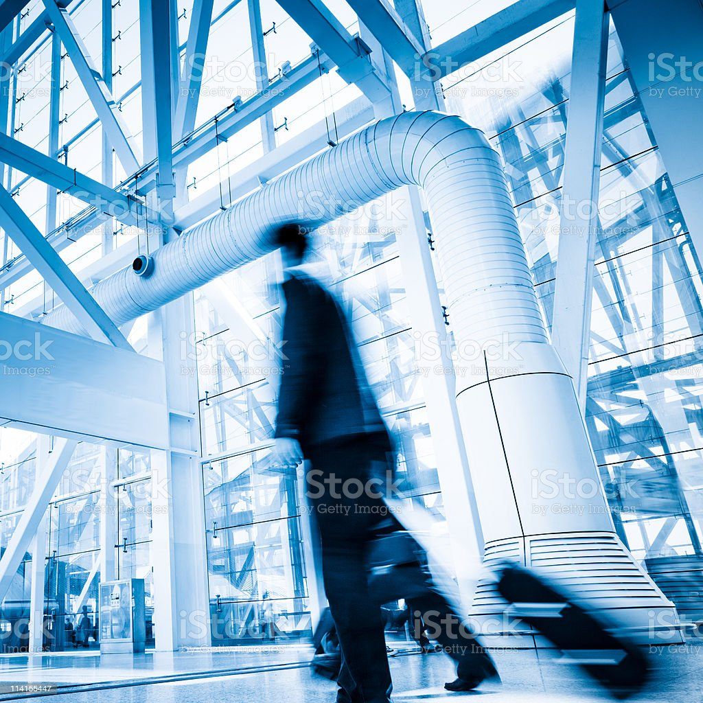 Blurred Travellers Pulling Suitcase Along Hallway in Airport royalty-free stock photo