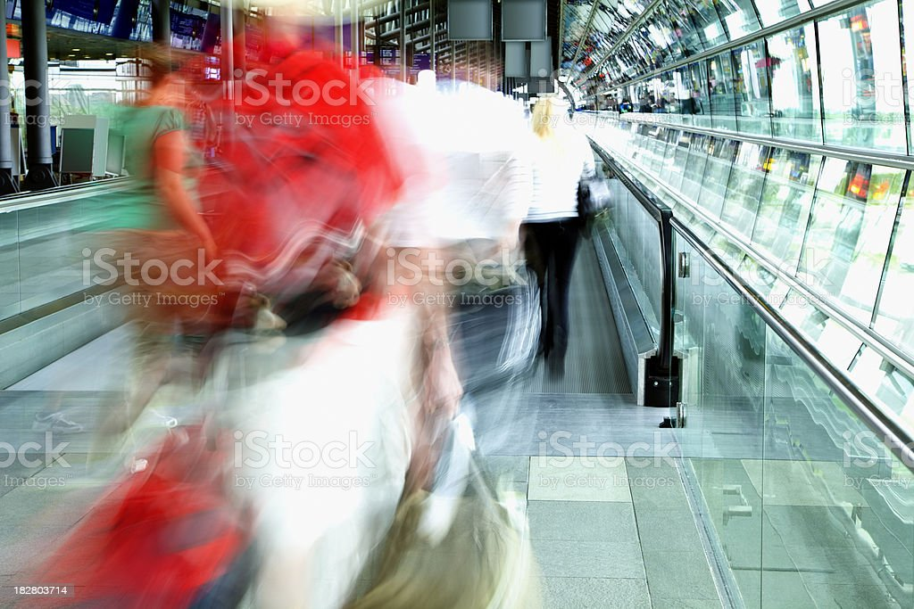 Blurred Travellers Walking Through Airport Hallway royalty-free stock photo