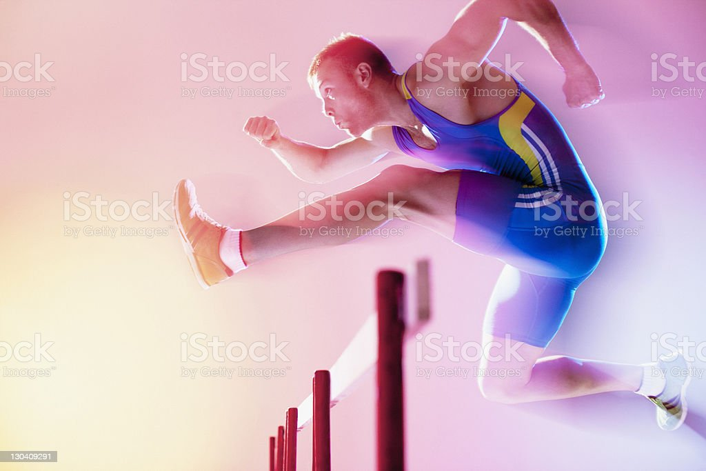 Blurred view of athlete jumping hurdles royalty-free stock photo