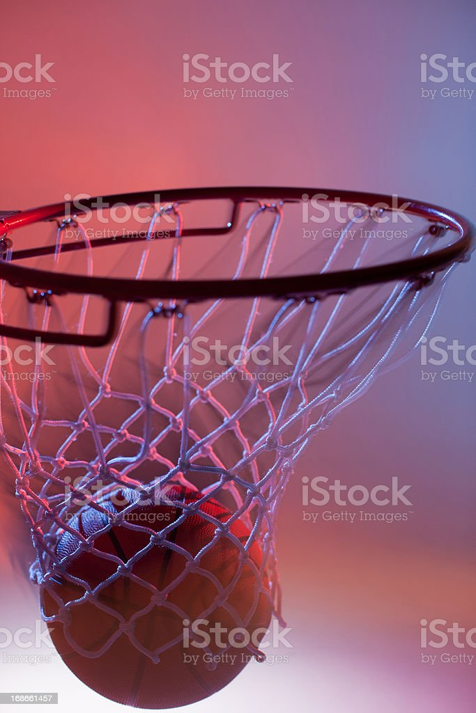 Blurred view of basketball going into hoop stock photo
