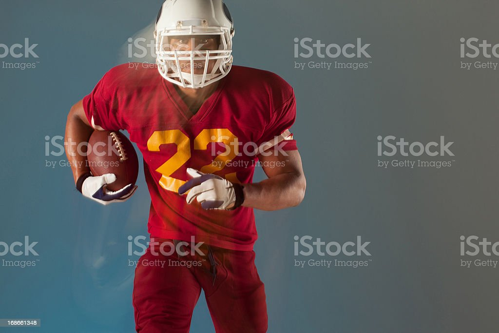 Blurred view of football player holding ball stock photo