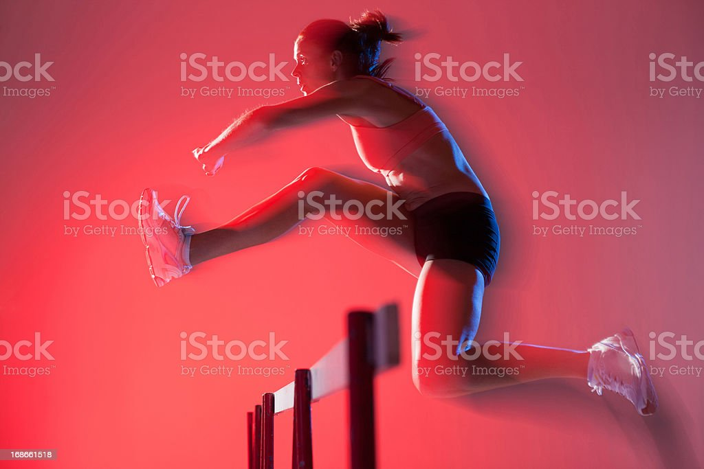 Blurred view of runner jumping hurdles royalty-free stock photo