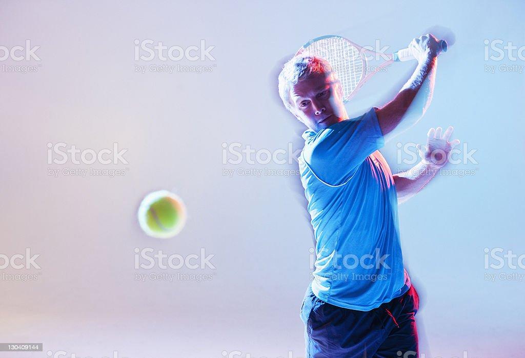 Blurred view of tennis player swinging racket stock photo