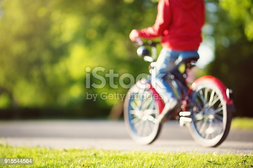 istock blurred view to a child on a bicycle at asphalt road 915544564