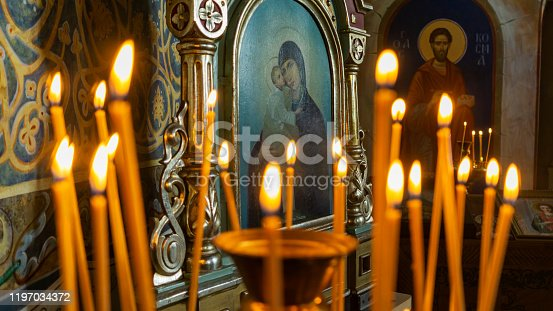 istock Blurred wax burning candles in an orthodox church on the icon background. 1197034372