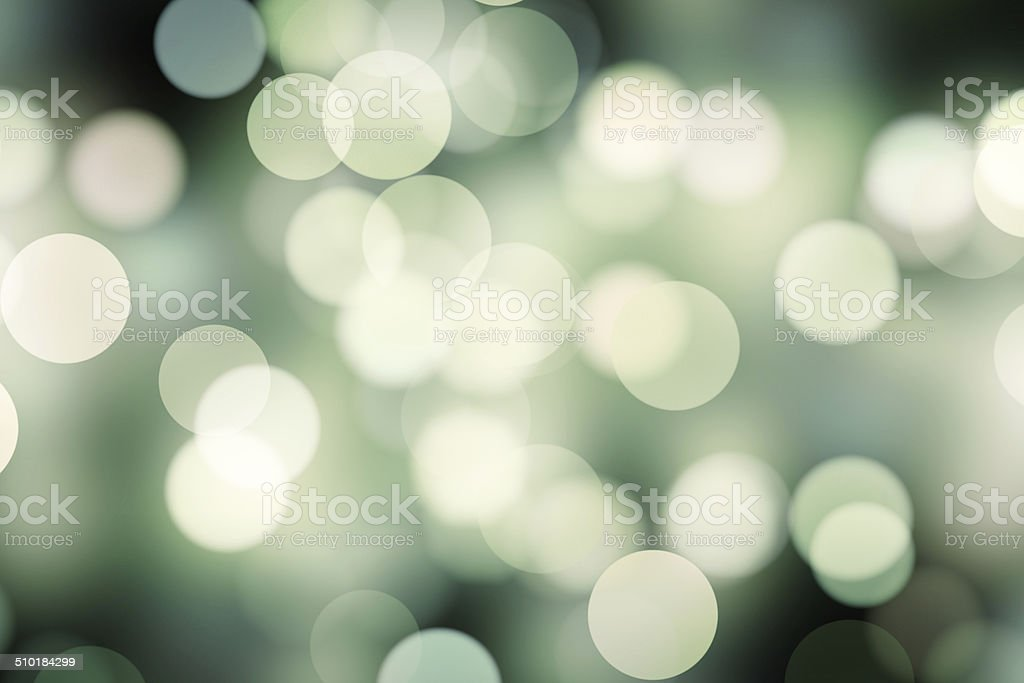 blurred white and green dots on black stock photo