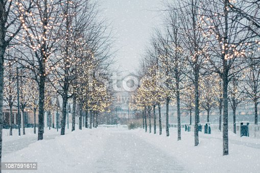 istock Blurred winter tree alley with falling snow and shining garlands in twilight. 1087591612