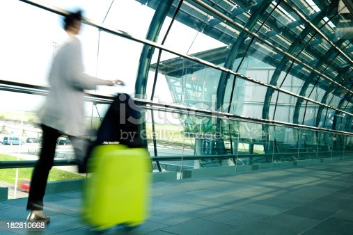 istock Blurred Woman Pulling Suitcase Allong Hallway in Airport 182810668