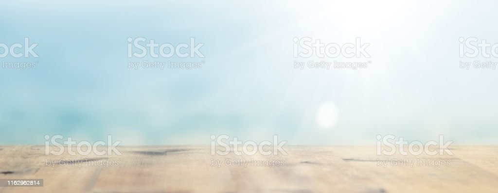Horizontal shot of blurred wooden empty table lit by soft sunlight....