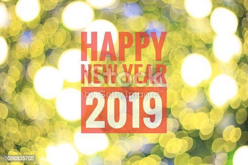 istock Blurred yellow bokeh lights as background, with red color text Happy New Year 2019. Holidays concept. 1056835702