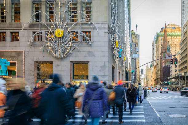 Blurred yellow taxi cabs speed past people and traffic cop at a busy crossing on 5th Avenue in Manhattan, New York, USA stock photo