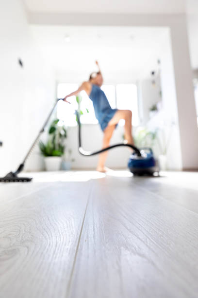 Blurred - Young housewife vacuuming in the house stock photo