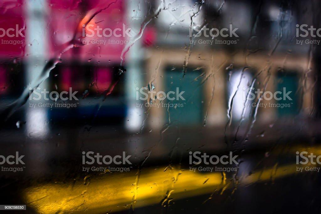 Blurry abstract rainy day, empty city street through bus window glass...