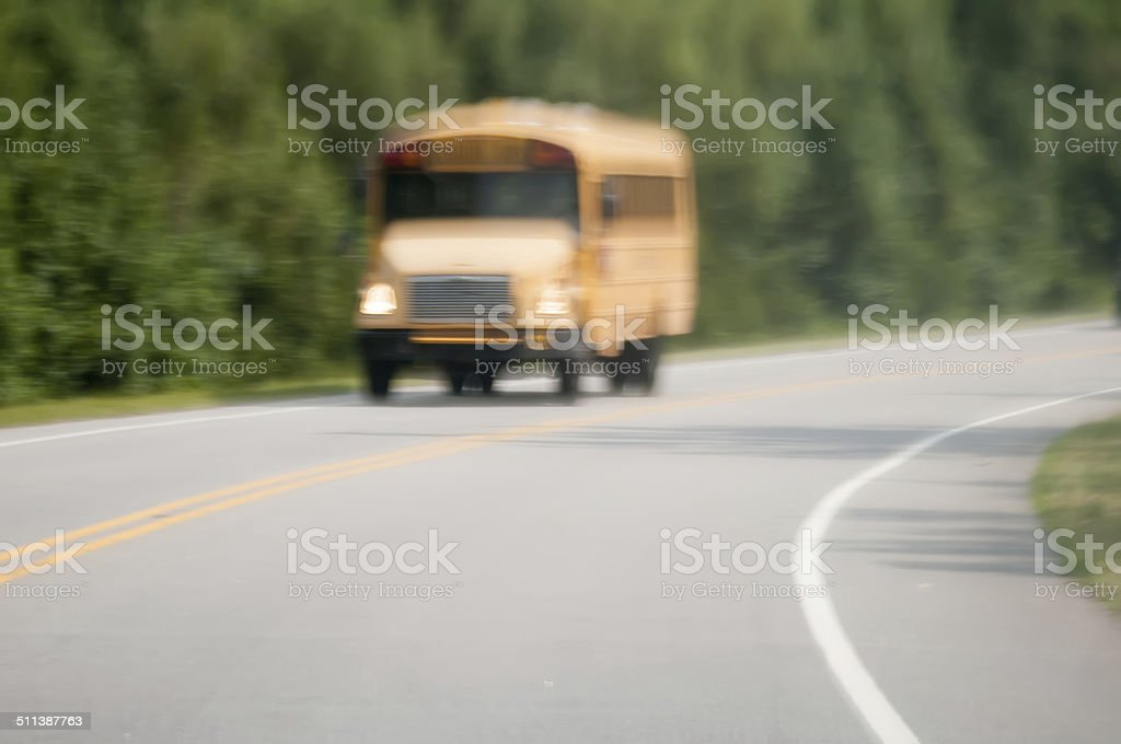 blurry abstract view of school bus driving on road stock photo