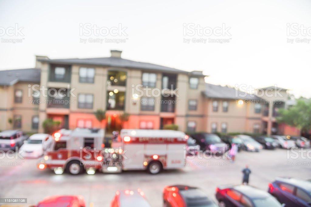 Blur high angle view fire trucks, firemen, resident at apartment fire...