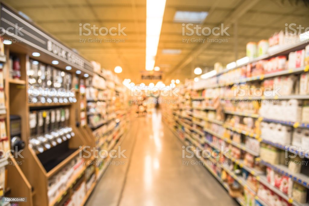 Blurred image of coffee, tea, juice, baking and nut butters aisle in...